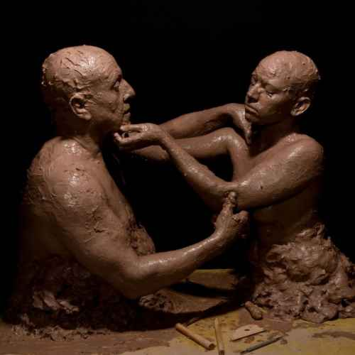 photograph of two people covered in clay